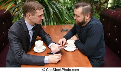 Two men at a cafe using a Tablet PC. upset