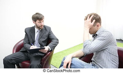 Sad young man talking with psychologist.