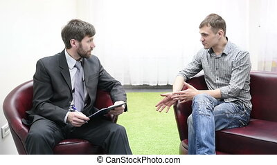 Sad young man talking with psychologist. Psychologist taking...