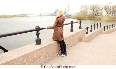 Young blond haired woman look back against port cranes and...