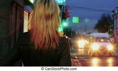 Young blond haired woman in nights street looking back toned...