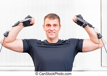 pretty strong man is engaged in a sports hall