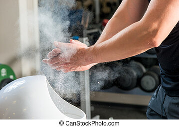 male weightlifter processes hands talcum powder against...