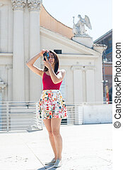 Young tourist woman taking picture with vintage camera outdoor