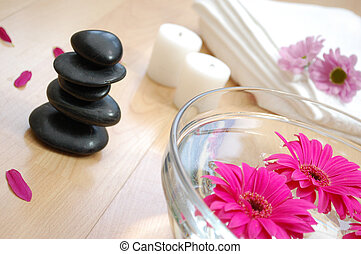 Therapy setting with zen stones, candles and a towel