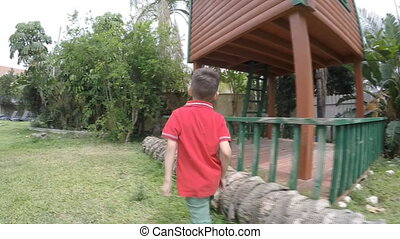 boy climbs on a wooden house slow motion