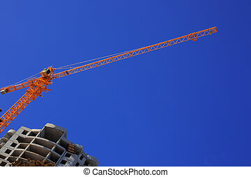 Construction crane against the blue sky building under...