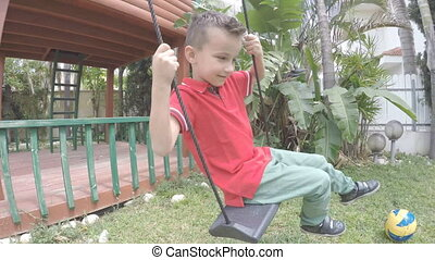 Boy spinning on tire swing, slow motion
