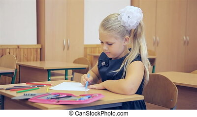 The girl draws in the classroom