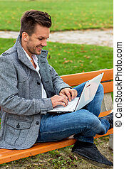 man with laptop in the park - a man with a laptop sitting on...