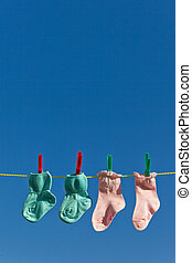 baby socks on clothesline to dry blue sky