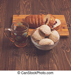 Cutted loaf with tea and buns - Tasty tea in a cup, buns in...