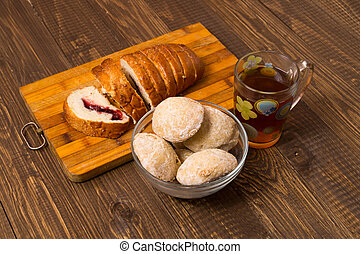 Buns with tea and cutted loaf - Tea in a cup, buns in dish...