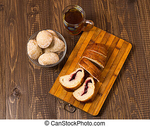 Cutted loaf with buns and tea - Tasty tea in a cup, buns in...