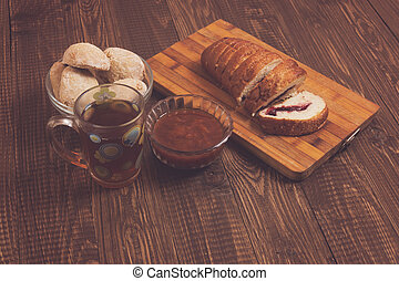 Buns with cutted loaf, tea and jam - Tea in a cup, buns in...