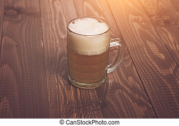 Frothy beer - The frothy beer is on the wood table