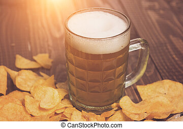 Frothy beer and crunchy chips - The frothy beer is next to...