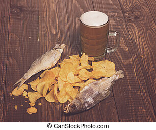 Fishes with frothy beer next to diffuse chips on the wood...