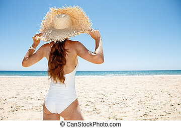 Seen from behind woman in white swimsuit and straw hat at...