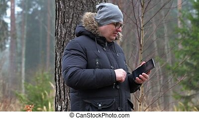Man with tablet PC looking for connection in forest