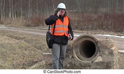 Engineer with smart phone at the concrete pipe