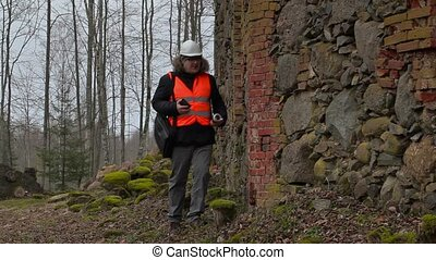 Building inspector with documentation checking old ruins