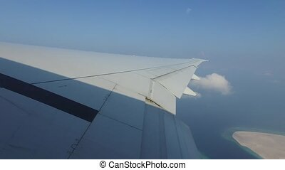 wing of airplane flying above ocean - travel,...