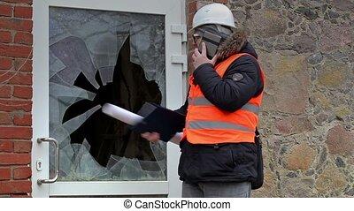 Building inspector with smart phone near broken window