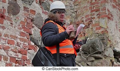 Building inspector checking brick at old ruins