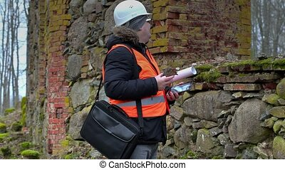Building inspector with stone near old ruins