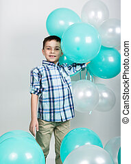 young man standing with his hands on hips, holding balloons...