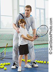 Instructor or coach teaching child how to play tennis on a...