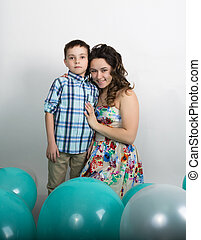 Brother kisses his sister around them lie balloons.