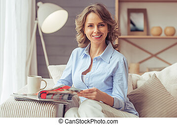 Beautiful woman at home - Beautiful woman is reading a...