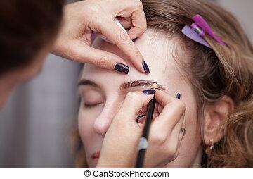 Cosmetologist applying permanent make up (tattoo) on...