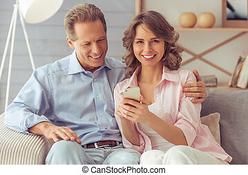 Beautiful couple with gadget - Happy beautiful couple is...