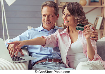 Couple doing shopping online - Happy beautiful couple is...