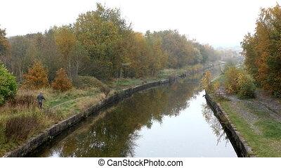 Man walking a dog on riverside - Tall man in wellingtons...
