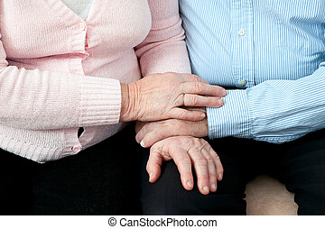 Older Couple Holding Hands. Elderly couple with beautiful hands posing together in  close embrace
