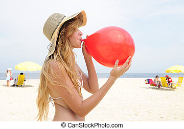 woman inflating a red balloon on the beach - party prewoman...