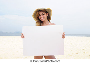 Advertising on the beach: woman showing blank board with...