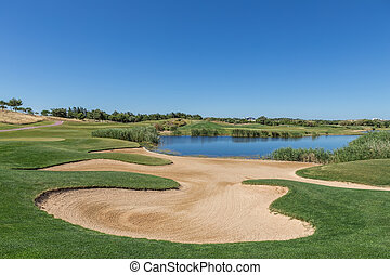 Sand trap on the golf course with a lake.