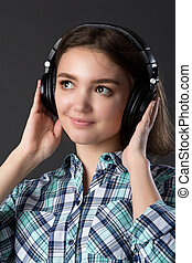 young girl listens to music with headphones