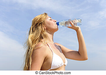 thirsty woman drinking water outdoors on a summer day