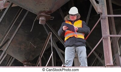 Engineer with documentation - Engineer with cell phone near...