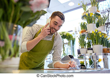 man with smartphone making notes at flower shop - people,...