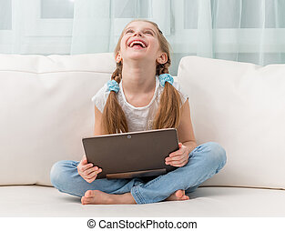 little girl laughs holding notebook on her crossed legs on...