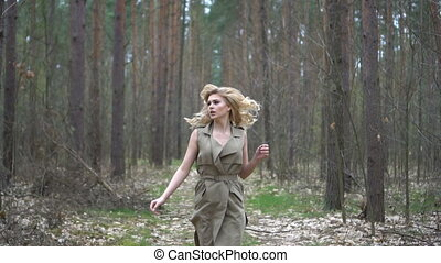 pretty blonde woman in the forest running away