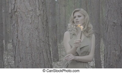 pretty blonde woman in the forest behind the trees
