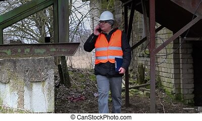 Engineer with cell phone at old factory